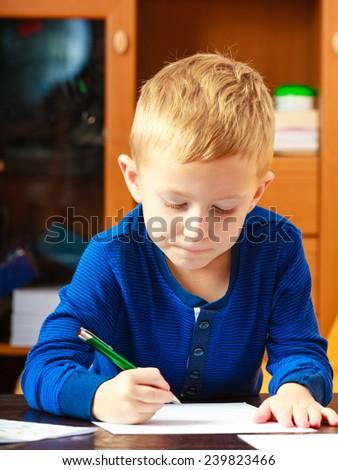 Happy childhood. Blonde boy child kid with pen writing drawing on paper doing homework. At home.