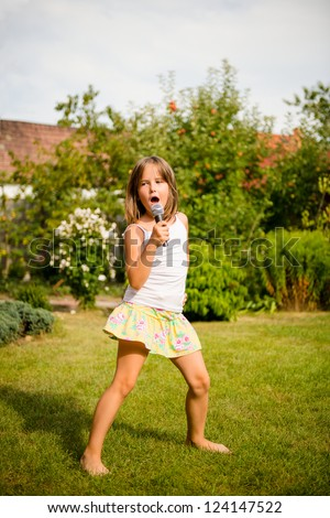 Happy childhood - child singing with microphone outdoor in backyard - stock photo