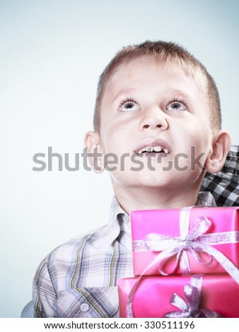 Happy childhood, holidays christmas time. Little boy child with pink presents gift boxes loking up. Positive emotion. - stock photo