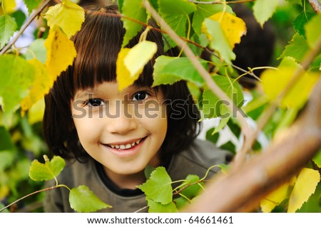 Happy childhood outdoor, happy faces between the leaves of the trees in forest or park, look for more in my porftolio - stock photo
