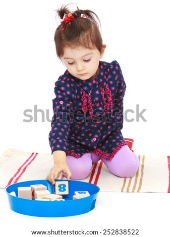 Happy childhood, the family concept.Cute little girl puts cubes sitting on the floor.Isolated on white. - stock photo