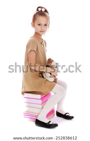Happy childhood, the family concept.Stylish little girl sitting on a pile of books. Isolated on white. - stock photo