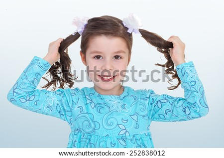Happy childhood, the family concept.The dark-haired little girl playfully tugged at his braids. - stock photo
