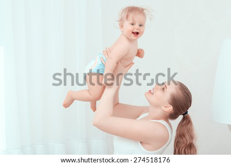 Happy childhood. Young happy mother throwing up her exited baby and laughing together  - stock photo