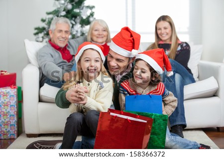 Happy children and father with gifts while family in background during Christmas at home - stock photo