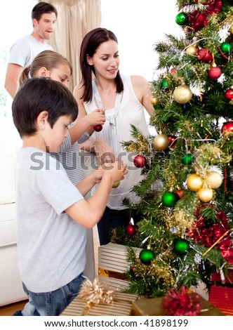 Happy children and parents decorating a Christmas tree in the living-room - stock photo