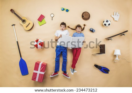 Happy children are reading book on the floor with group of objects around them - stock photo
