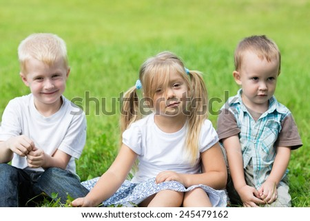 Happy children are resting on the lawn. Brothers and sister. - stock photo