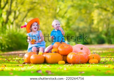 Happy children at pumpkin patch during Halloween, little girl in a blue dress, boots and cowboy hat and baby boy having fun together trick or treating on a sunny autumn day - stock photo