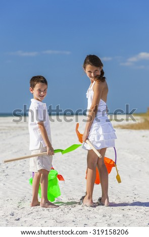 Happy children, boy girl, brother and sister having fun playing in the sand on a beach with bucket and spade