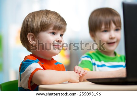 happy children boys playing at laptop at home - stock photo