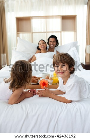 Happy children bringing a breakfast to their parents in the bedroom - stock photo