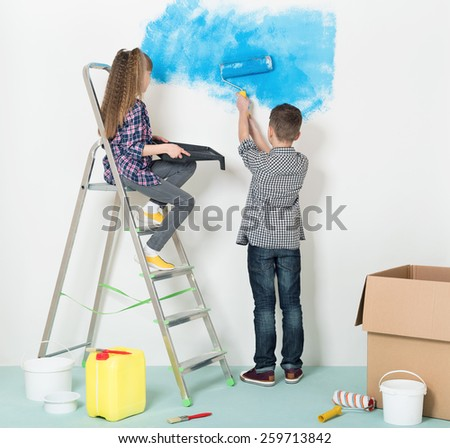 Happy children -  brother and sister, makes repairs at home. Boy and girl painting wall at home. - stock photo