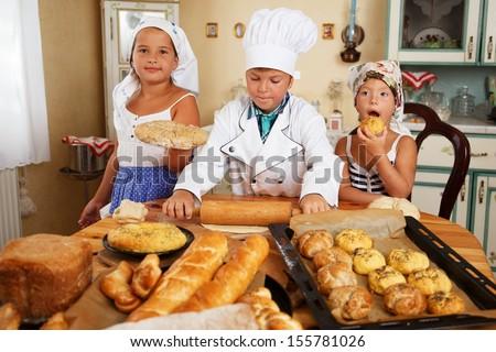 Happy children cooking homemade pastry - stock photo