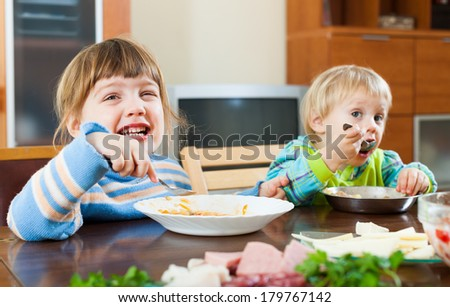 happy children eating food at wooden table - stock photo