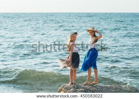 Happy children girls running on a beach - stock photo