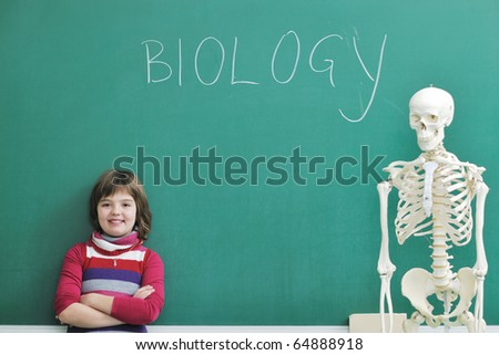 happy children group  in school classrom taking notes and learning biology and anatomy lessons with teacher - stock photo