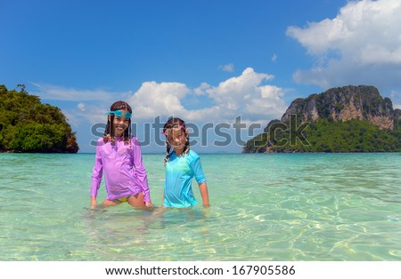 Happy children having fun in sea near tropical island, kids on beach vacation  - stock photo