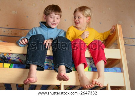 Happy children in child's room on a bunk-beds - stock photo