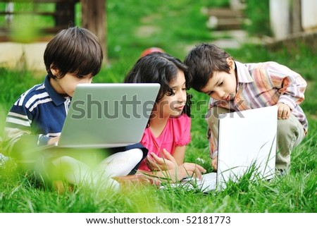 happy children in nature with laptop - stock photo