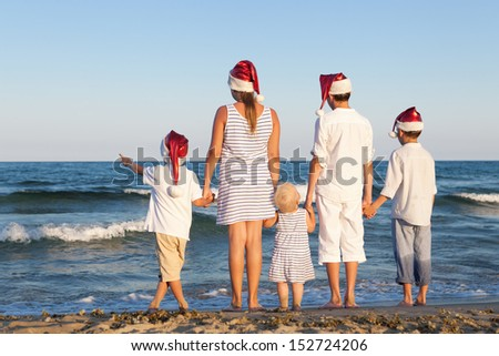 HAppy Children in santa claus hat  are standing on beach, outdoor