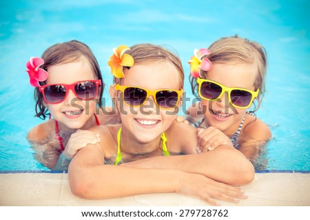 Happy children in the swimming pool. Funny kids playing outdoors. Summer vacation concept - stock photo