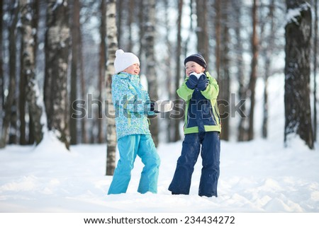 Happy children in winter day play with snow. - stock photo