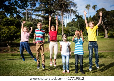 Happy children jumping in the park on a sunny day - stock photo