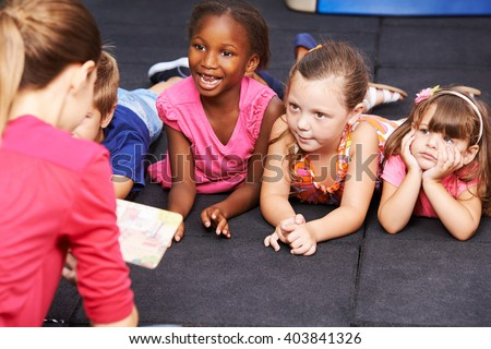 Happy children listening to fairytale book in preschool read by nursery teacher - stock photo