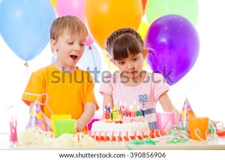 Happy children look at birthday cake - stock photo