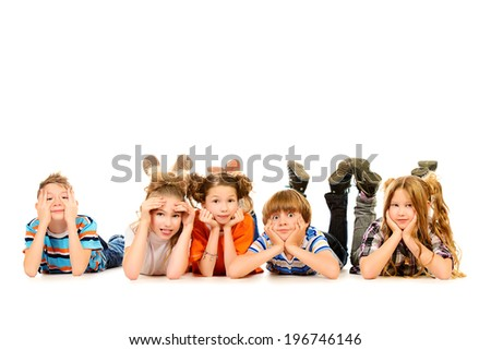 Happy children lying on a floor and smiling at camera. Isolated over white. - stock photo