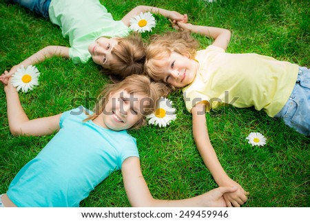 Happy children lying on grass. Funny kids playing in park. Beautiful spring flowers. Top view - stock photo