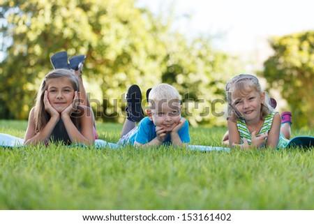 Happy children of three lying in grass springtime - stock photo