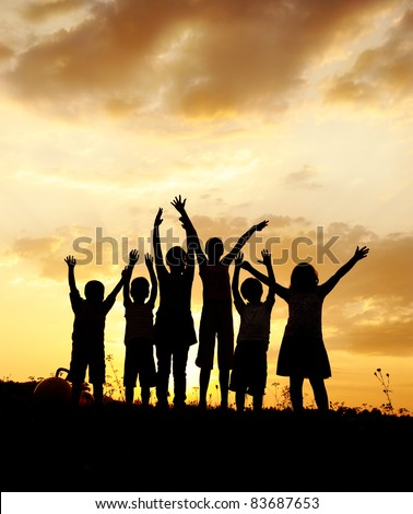 Happy children on meadow, sunset, copy space above - stock photo