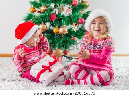 Happy children open Christmas presents on the floor and tree with New Year decoration at home.