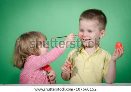 Happy children   painting Easter eggs and each other on nose against green background  - stock photo