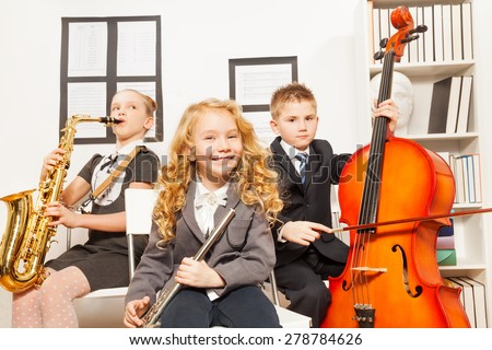 Happy children play musical instruments together - stock photo