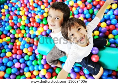 Happy children playing and having fun at kindergarten with colorful balls - stock photo