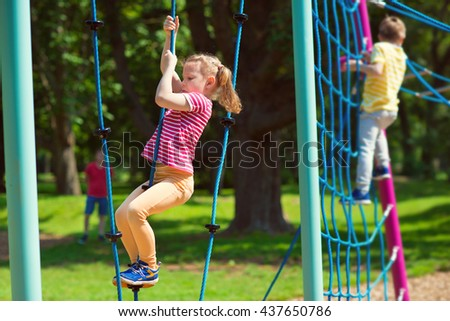 Happy children playing at playground in summer day - stock photo