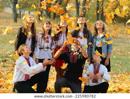 happy children playing autumn leaves in the park - stock photo