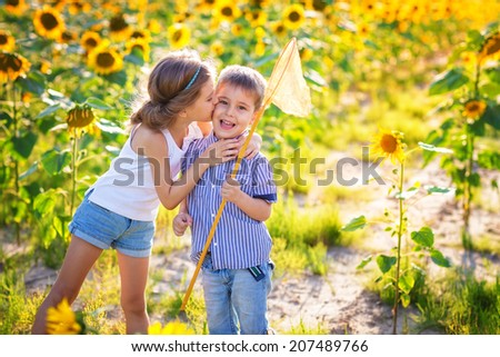 Happy children playing on sunflower field - stock photo