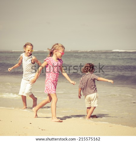 Happy children playing on the beach at the day time - stock photo