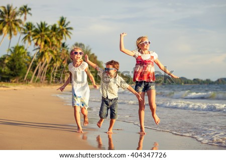 Happy children playing on the beach at the day time. Concept of happy friendly sister and brother. - stock photo