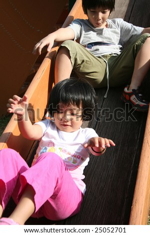 Happy children playing slide at the playground in the park on sunny day - stock photo