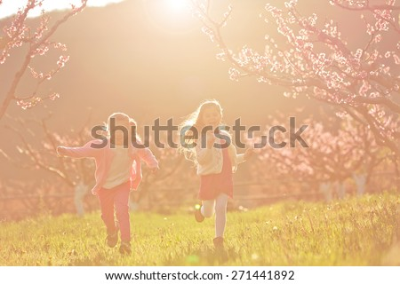 Happy children running at meadow, Vintage Color. Sunset light