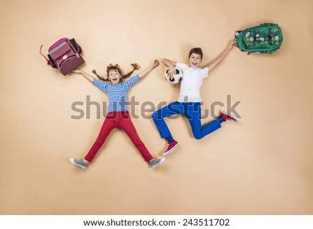 Happy children running to school in a hurry. Studio shot on a beige background. - stock photo