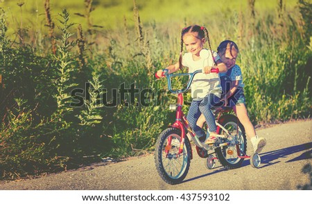 happy children sister  girl cyclist riding a bike on the road - stock photo