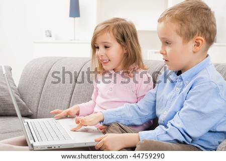 Happy children sitting on couch at home, browsing internet on laptop computer, looking at screen smiling. - stock photo