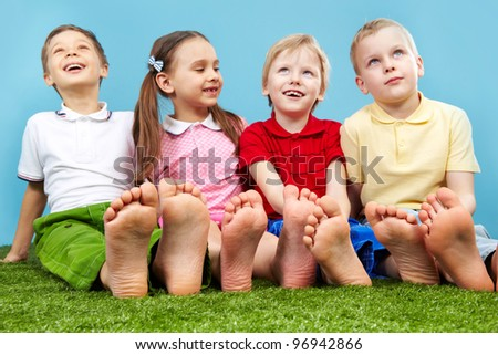 Happy children sitting on the lawn barefoot - stock photo