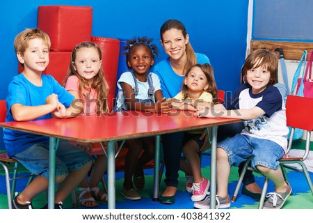 Happy children sitting together with nursery teacher at table in kindergarten - stock photo